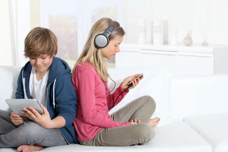 addiction: Teenagers sitting in sofa with electronic devices