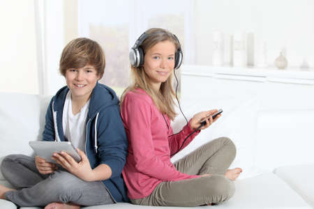 android tablet: Teenagers sitting in sofa with electronic devices