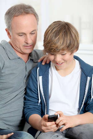 smartphone addiction: Father and son playing with mobile phone Stock Photo