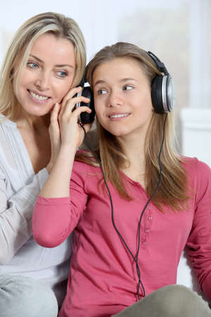 Mother and daughter listening to music whit headphones photo