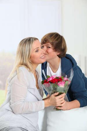 mama e hijo: Hijo ofreciendo manojo de flores en el cumplea�os de la madre