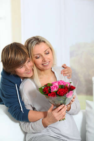 Son offering bunch flowers on mothers birthday photo