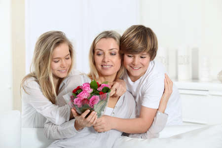 Children offering bunch of flowers on mothers day photo