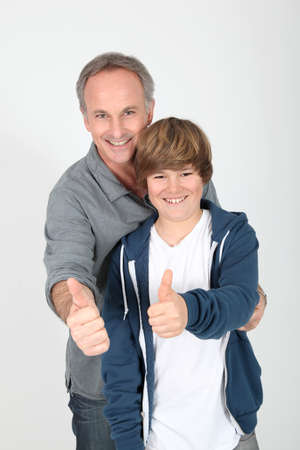 Father and son standing with thumbs up photo