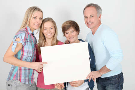 Portrait of happy family holding whiteboard photo