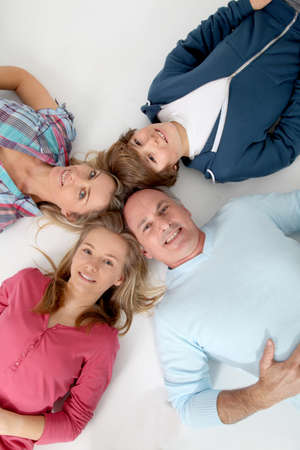 Upper view of family of 4 people laying on the floor photo