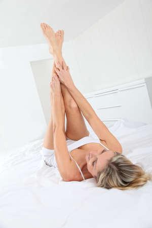 piernas mujer: Mujer rubia tendido en la cama con patas