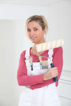 housepainter: Beautiful blond woman with paint roller
