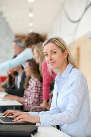 teacher working on laptop computer in classroom photo