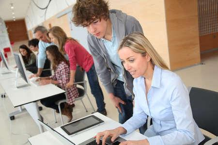 profesor alumno: Profesor y adolescente en frente del ordenador port�til Foto de archivo