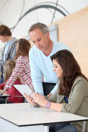 Teacher and teenage girl working on electronic tablet  photo
