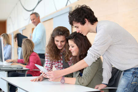 adolescentes estudiando: Grupo de adolescentes en aula con tableta electr�nica Foto de archivo