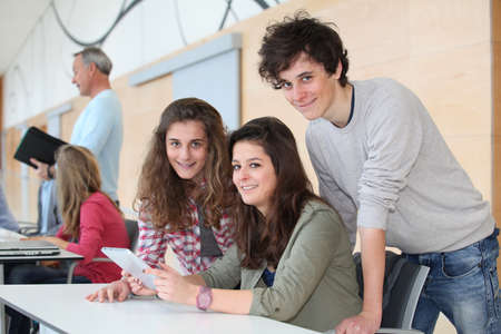 traineeship: Group of teenagers in classroom with electronic tablet Stock Photo