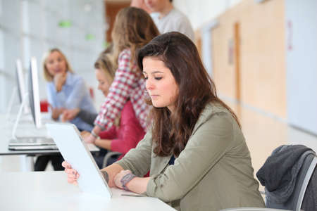Teenage girl at school using electronic tablet photo
