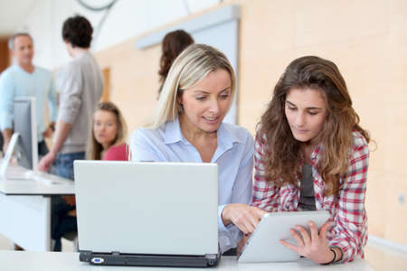trainees: Portrait of teacher and teenage girl in computing class