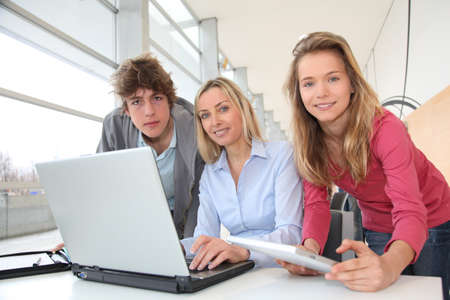 Teacher and students working on laptop computer at school photo