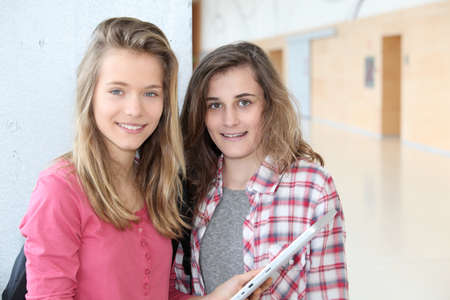 Teenage girls using electronic tablet at school photo