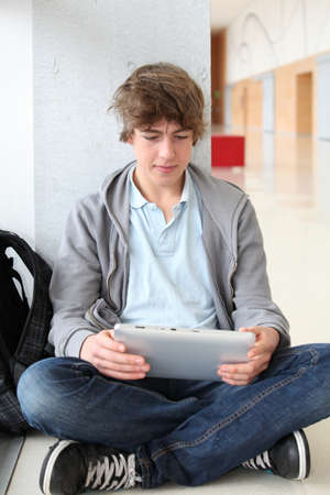 School boy with electronic tablet sitting in hall photo