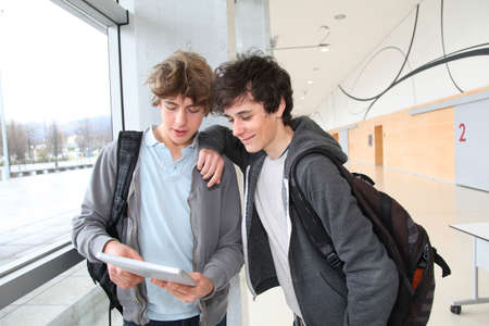 android tablet: Teenage boys using electronic tablet in school hall