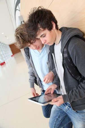 Teenage boys using electronic tablet in school hall photo