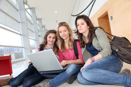 Group of teenage girls at school with laptop computer photo
