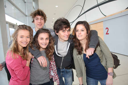 school teens: Group of classmates standing in school entrance hall Stock Photo