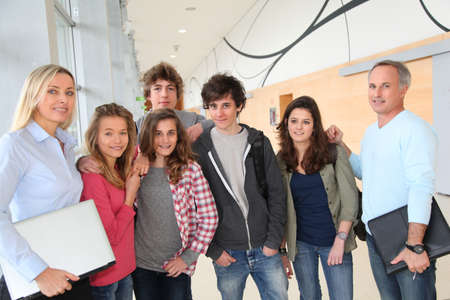 teachers: Portrait of teenagers and teachers standing on school hall Stock Photo