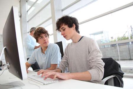 Teenagers in classroom working on desktop computer photo