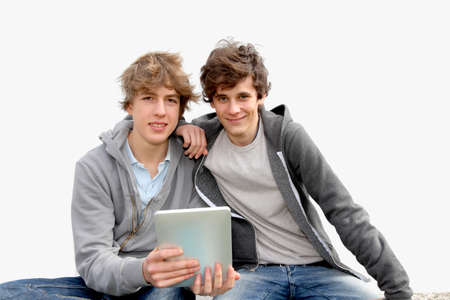 Teenage boys sitting outside with electronic tablet photo