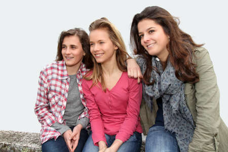 Group of teenagers sitting on school bench photo