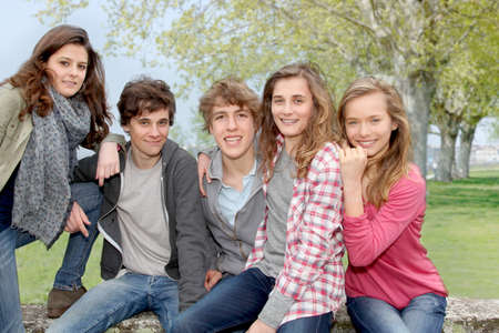 Group of teenagers sitting outside photo