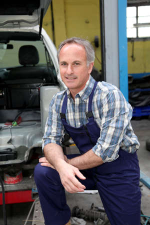 Portrait of garage owner standing by vehicle photo
