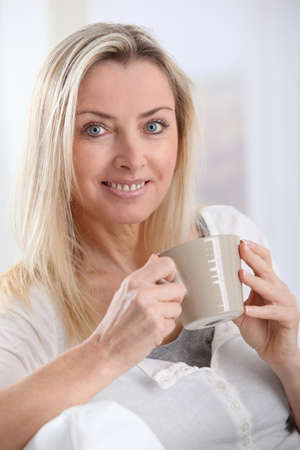 Portrait of beautiful blond woman drinking tea photo