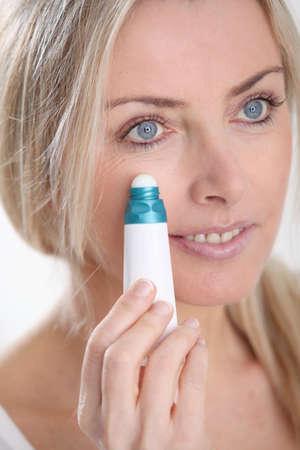 serum: Blond woman applying anti-aging serum on her skin
