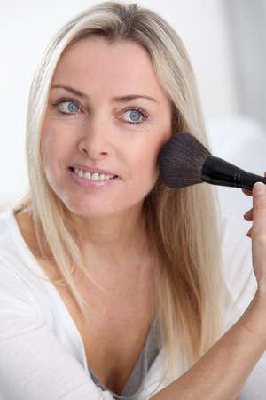mujer maquillandose: Hermosa mujer rubia aplicar maquillaje en su cara