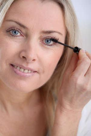 Closeup of woman applying mascara on eyelashes photo