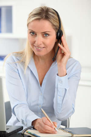 noting: Blond woman in the office with headset on