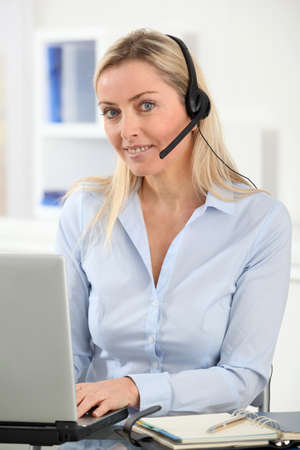 teleoperator: Blond woman in the office with headset on