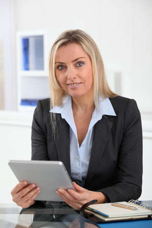 blonde yeux bleus: Businesswoman in the office with electronic tablet