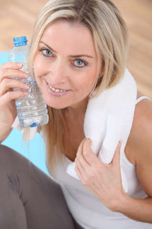 Beautiful blond woman drinking water after exercising photo