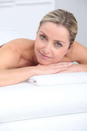 Beautiful adult blond woman on massage bed photo
