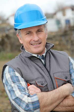 Portrait d'ingénieur souriant avec casque de sécurité bleu