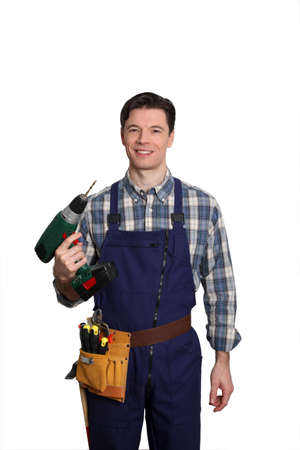 Carpenter standing on white background with electric drill Stock Photo - 9097748