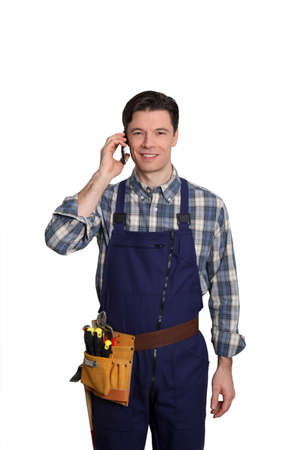Carpenter standing on white background with mobile phone Stock Photo - 9097330