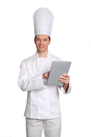Chef standing on white background with electronic tablet photo