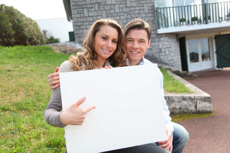 Couple holding whiteboard in front of their house 写真素材