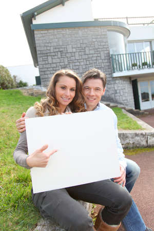 man holding woman: Couple holding whiteboard in front of their house Stock Photo