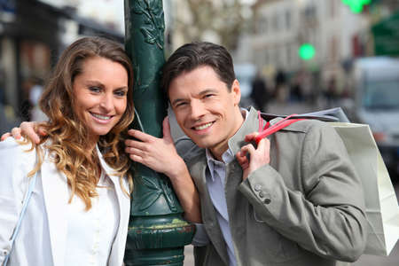 Couple holding shopping bags in town photo
