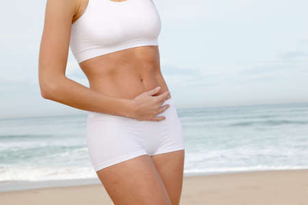 sculpt: Closeup of womans body stretching on the beach Stock Photo