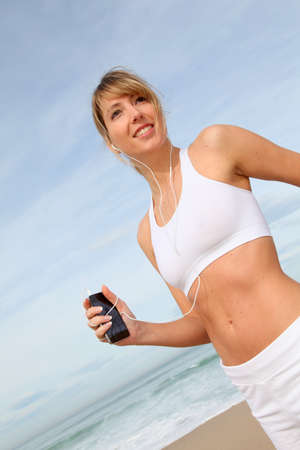 Woman jogging on the beach with music player photo